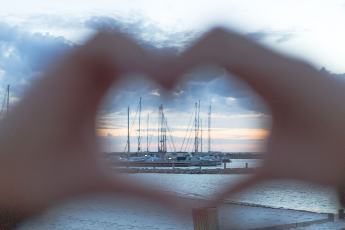 Two hands creating the shape of a heart with a harbor and a sunset in the background.