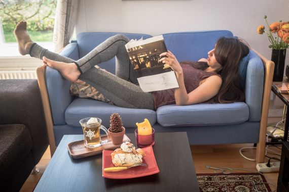 Arina lying on a blue couch reading a magazine with a cake and a cup of tea on the table in front of her