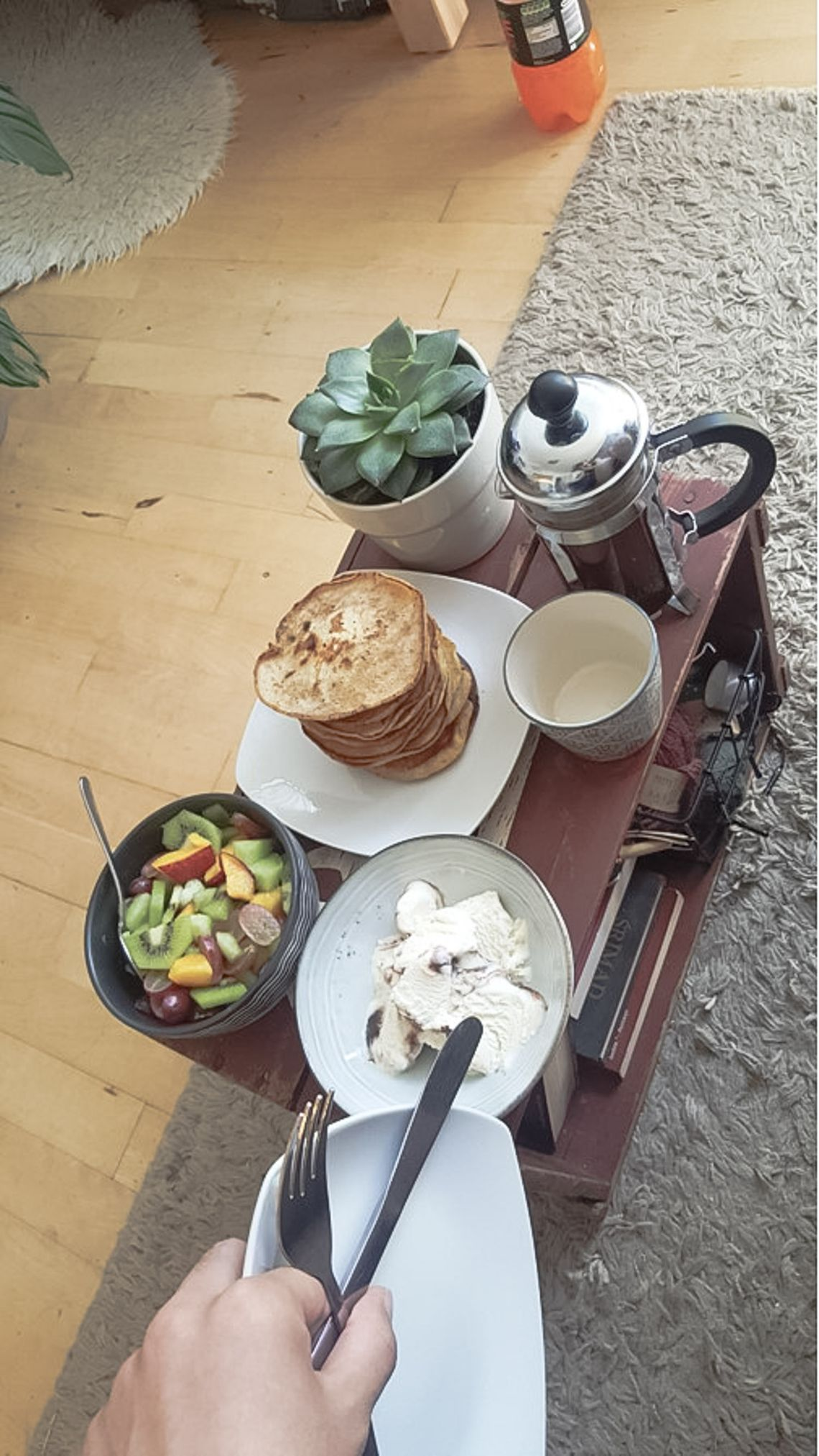 A table with a plant, coffee, pancakes, a bowl of fruit and icecream.
