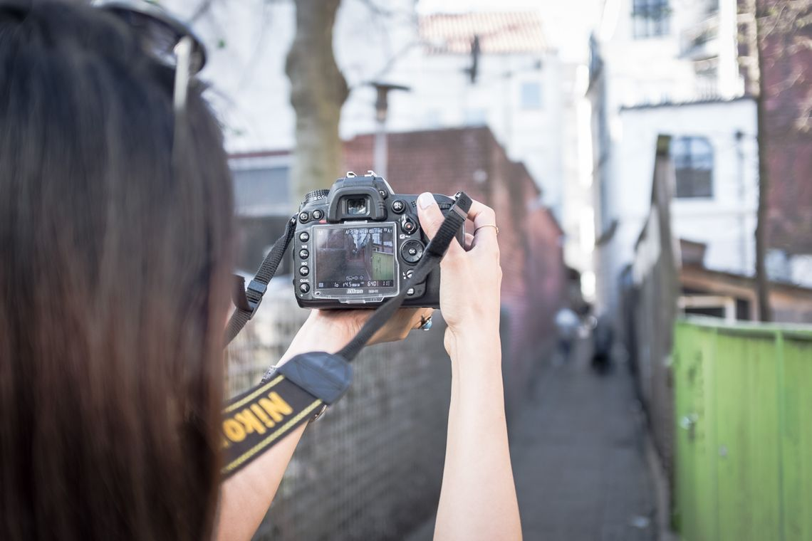 Arina holding a Nikon camera up in front of her, taking photos of an alley