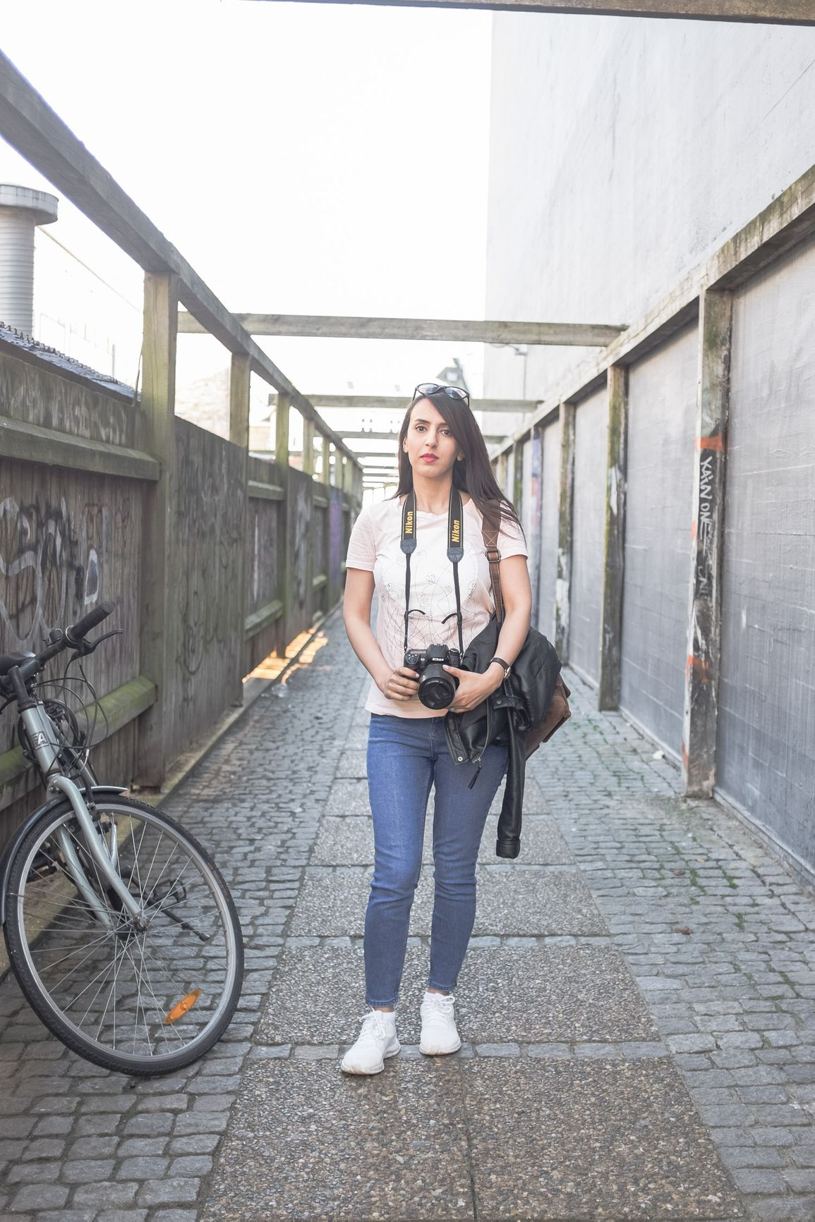 Arina standing with a Nikon camera in an alley with her bike next to her