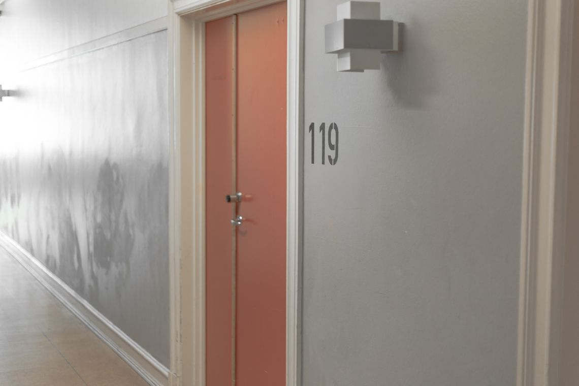 A red door in a grey hallway with the number 119 written in black letters next to it.