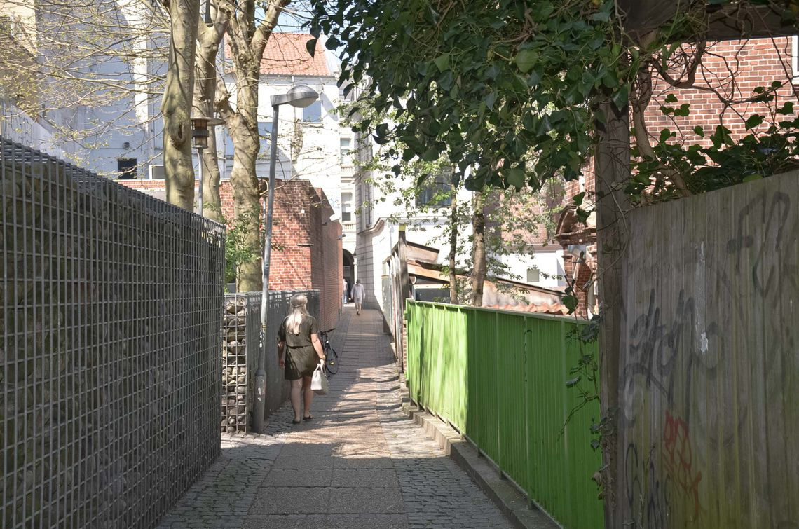 An alley with a green fence and a woman walking away from the camera