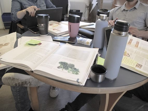 A table with open books placed on it and coffee cups.