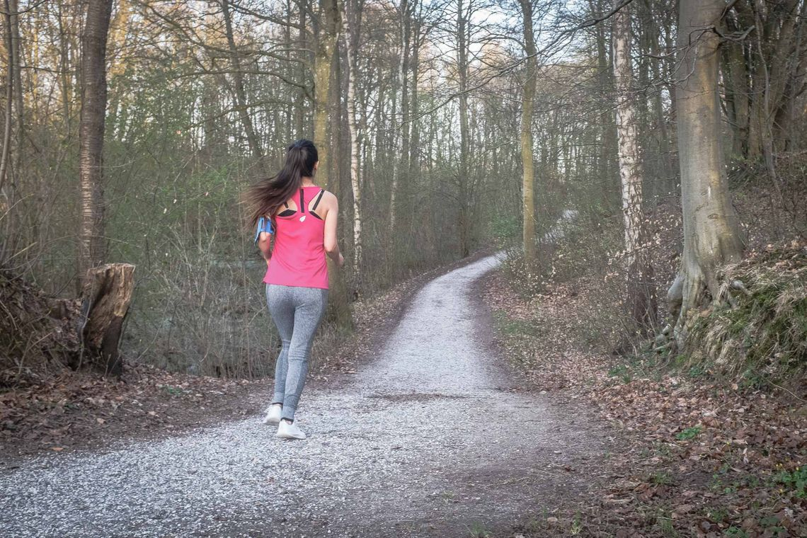 Arina running while listening to music on a gravel path in a forest