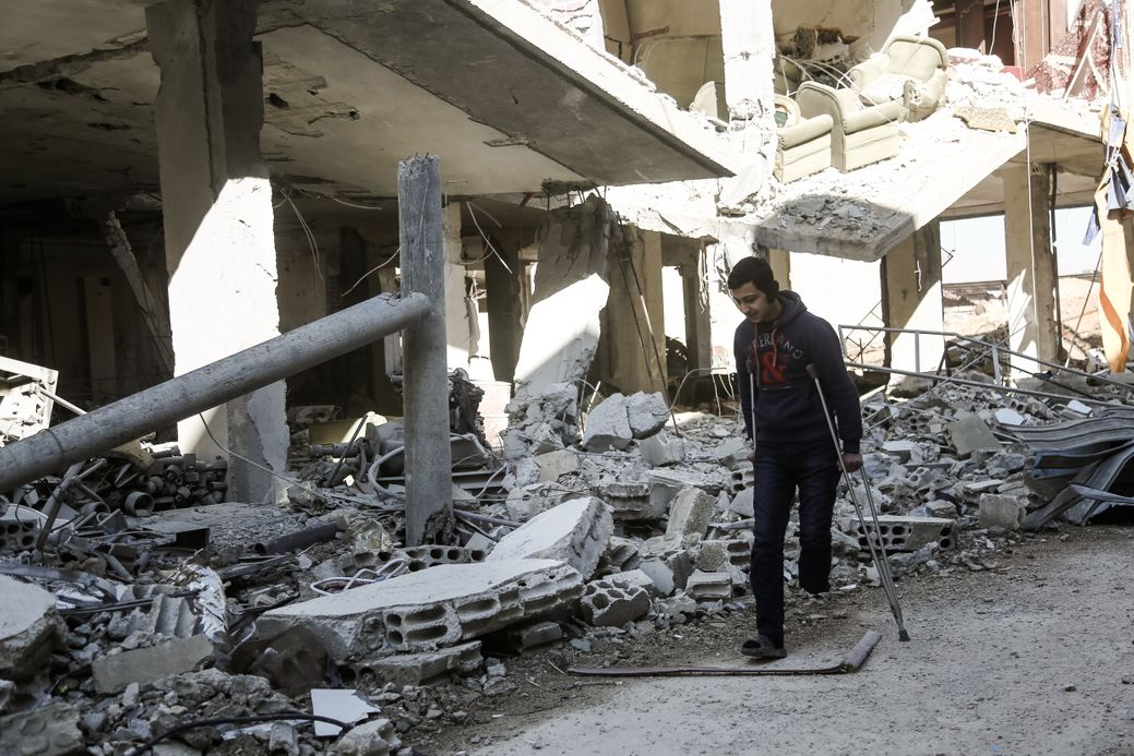 Photo by Salem Mdlala. A young man walking with crutches next to a destroyed building in Ghouta.