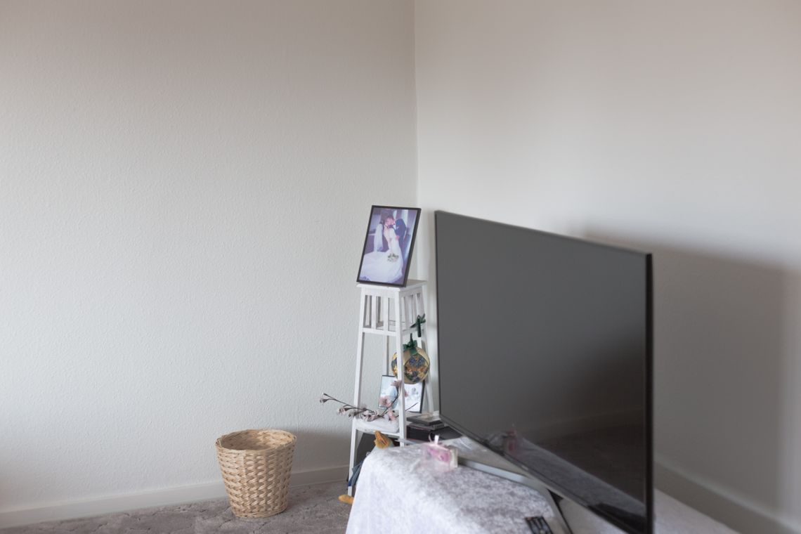 A television and a wedding photo in the corner of a white room.